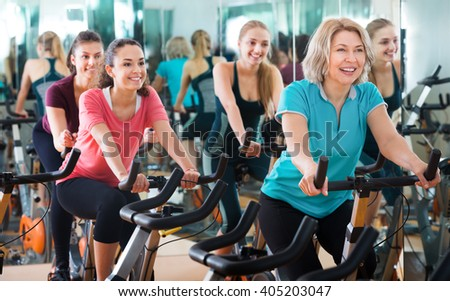 Positive females of different age training on exercise bikes together in modern fitness club  - stock photo