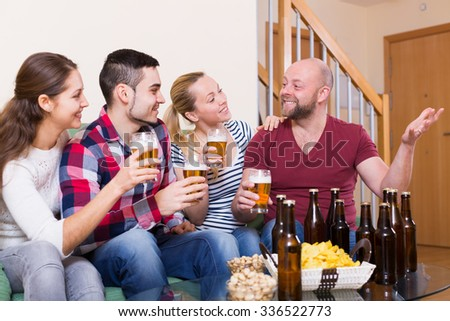 Positive friends hanging out with beer and snacks at the home  - stock photo