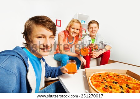 Positive friends hold glasses and ready for pizza - stock photo