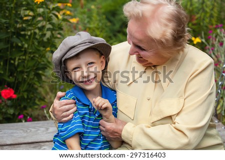 Positive grandmother and grandson spent time together in summer solar garden.  - stock photo