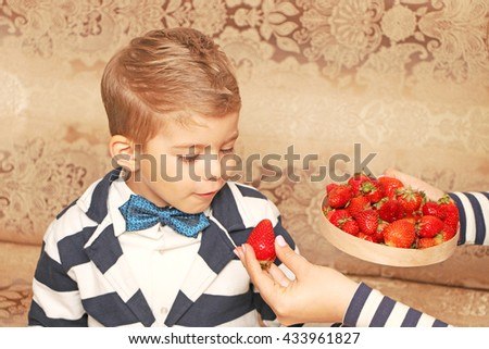 Positive handsome  small style boy with fashion hairdo looking at big juicy ripe strawberries and wants to taste and eat it. - stock photo