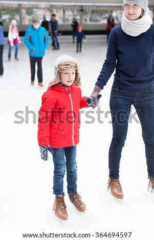positive happy boy and his mother enjoying winter vacation at outdoor ice skating rink  - stock photo