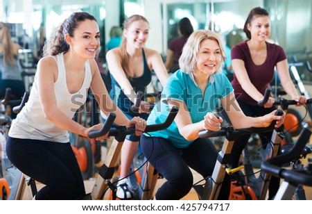 Positive happy females of different age training on exercise bikes together in fitness club  - stock photo