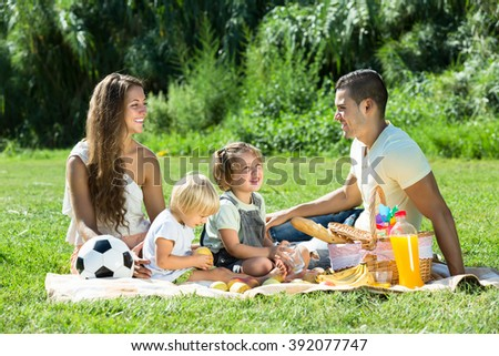 Positive happy smiling family of four on picnic at summer day