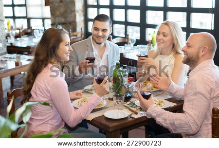 Positive happy young people enjoying a food and smiling at tavern  - stock photo