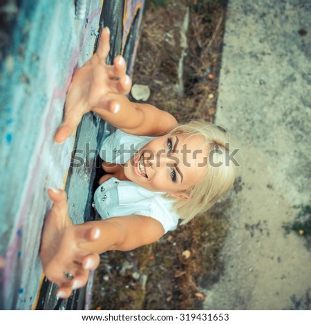 Positive hipster girl. portrait of a beautiful young hipster girl which climbs upwards. view from above - stock photo