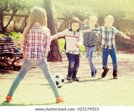 Positive kids playing street football outdoors in spring day - stock photo