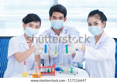 Positive lab interns demonstrating test-tubes full of chemical reagents - stock photo