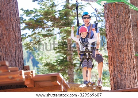 positive little boy and his father climbing at outdoor treetop adventure park being active and healthy together - stock photo