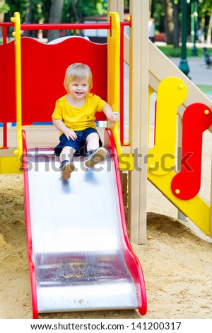 Positive little boy is about to go down from the slide on playground - stock photo