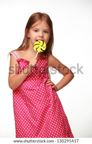 Positive little girl in a summer dress eating a large yellow lollipop on white background - stock photo