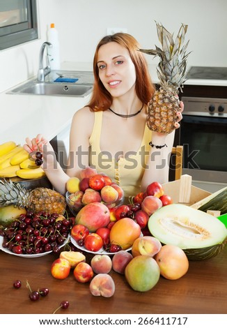 Positive long-haired woman with pine and heap of ripe fruits in home kitchen  - stock photo