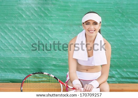 Positive Looking Professional Female tennis Player having rest on Bench of Tennis Court and Smiling. Horizontal Image - stock photo