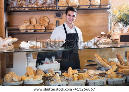 Positive male bakery employee offering different pastry for sale - stock photo