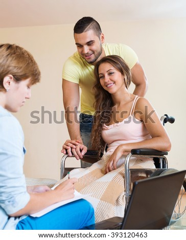 Positive man and handicapped wife on wheelchair having discussion with agent - stock photo