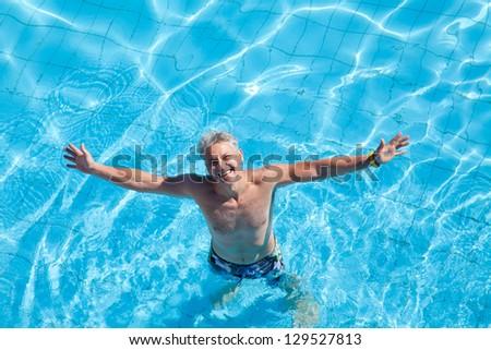 Positive man enjoying in the swimming pool - stock photo