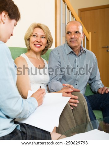 Positive mature couple filling questionnaire for employee in the living room  - stock photo