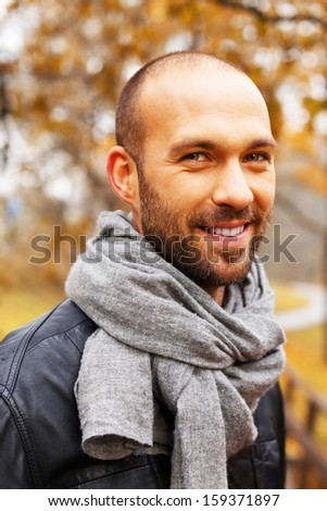 Positive middle-aged man alone on beautiful autumn day - stock photo
