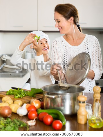 Positive mother and her cheerful daughter preparing soup together at kitchen