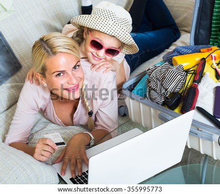 Positive mother with little daughter buying tickets for long-awaited vacation online