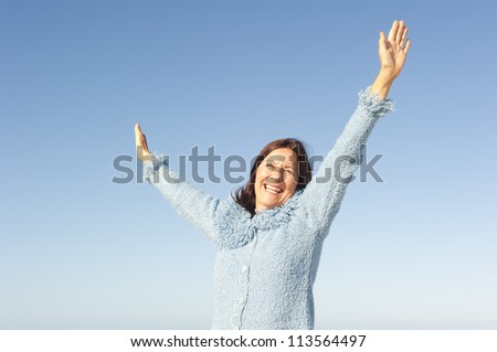 Positive, optimistic and happy active retired senior woman posing with arms up and smile, isolated with blue sky as background and copy space. - stock photo