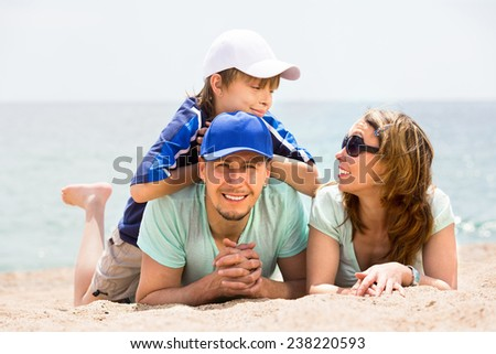 Positive parents with smiling boy in vacation at seaside - stock photo