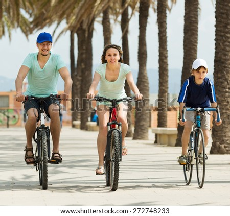 Positive parents with son riding bicycles and smiling - stock photo