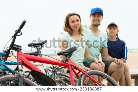 Positive parents with son sitting on sand with bicycles  at seaside - stock photo