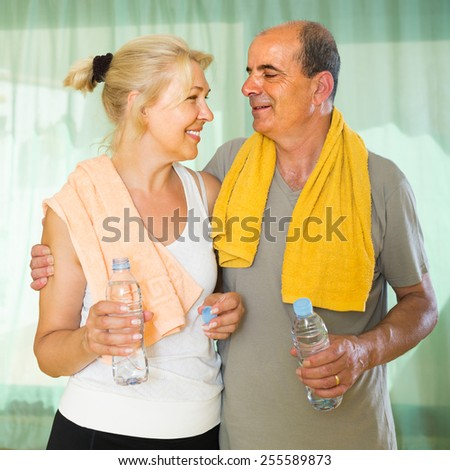 Positive pensioners with bottles of water after morning exercises   - stock photo