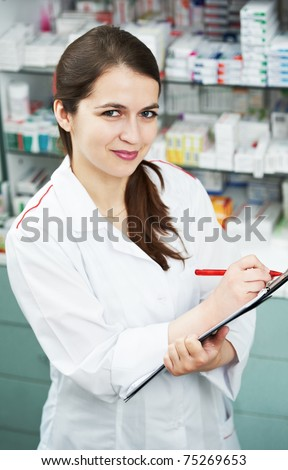 positive pharmacist chemist woman standing in pharmacy drugstore with clipboard - stock photo