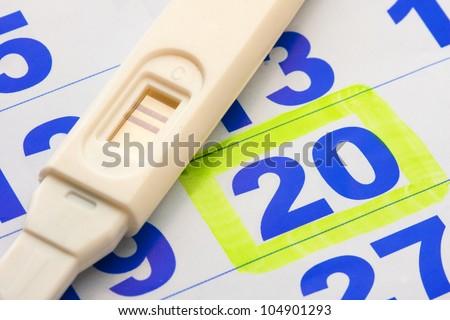 Positive pregnancy test on calendar page - stock photo