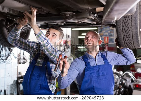 Positive russian mechanics fixing car tire leak  - stock photo