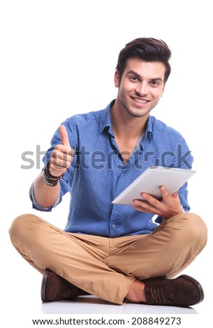 positive seated casual man with tablet pad computer making the ok thumbs up hand sign - stock photo