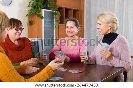 Positive senior female friends enjoy  bridge at home - stock photo