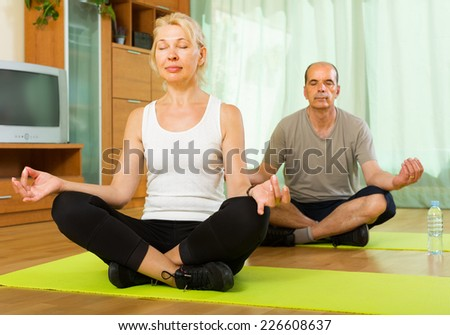 Positive senior mature couple doing asana in the living room at home - stock photo