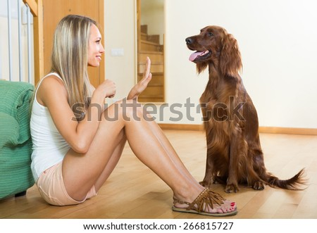 Positive smiling adult girl sitting on floor with red Irish setter