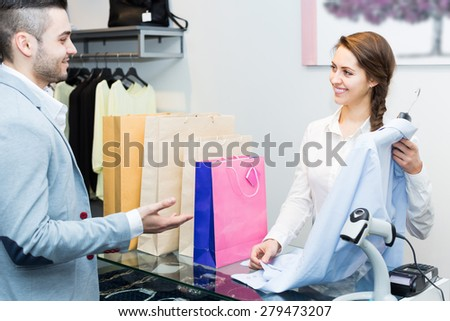 Positive smiling customer paying for new apparel at store counter  - stock photo