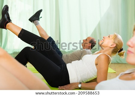 Positive smiling elderly couple practicing body bending at gym  - stock photo