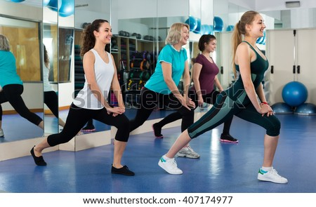 Positive smiling females having gymnastic class in fitness club . Selective focus