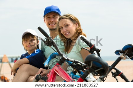 Positive smiling parents and boy with bicycles at seashore - stock photo