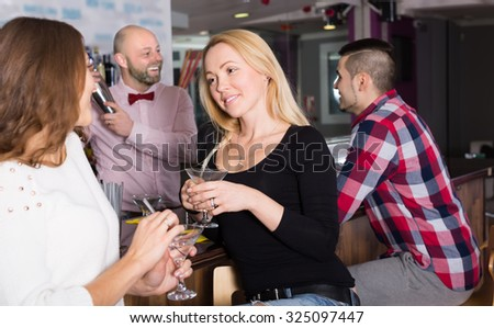 Positive smiling young adults hanging out in bar - stock photo