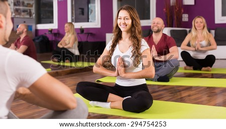 Positive smiling young adults having yoga class in sport club - stock photo