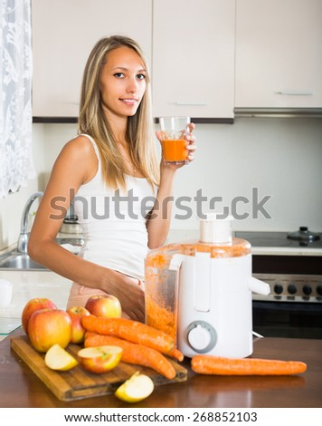 Positive smiling young woman preparing fresh juice in domestic kitchen - stock photo