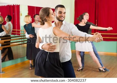 positive spanish men and women enjoying of tango in class  - stock photo