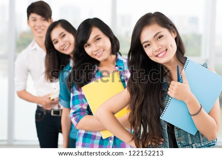 Positive students standing in a row and looking at camera - stock photo