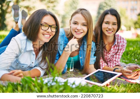 Positive teenage girls with technological devices spending leisure in park - stock photo