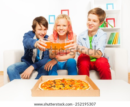 Positive teens holding glasses with juice on sofa - stock photo
