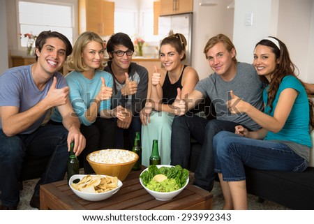 Positive thumbs up group of friends gathered at home sitting in living room for a party celebration holiday - stock photo