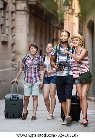Positive travelers walking the street and watching showplace - stock photo