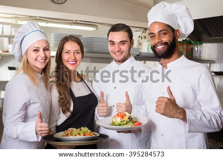 Positive waitress and cooking team at professional kitchen in restaurant - stock photo